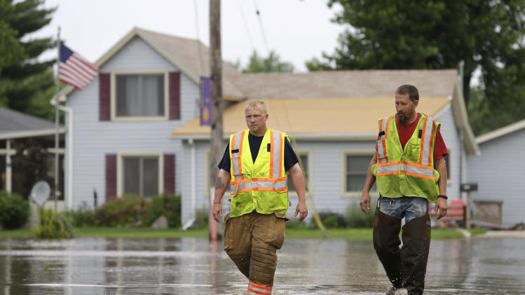 New Hartford firefighters Clint Olmstead, left, and Jon LeBahn walk through floodwaters, Tuesday, June 25, 2013, in New Hartford, Iowa. Hundreds of residents obeyed an order to evacuate their homes in this northeast Iowa town Tuesday before floodwaters from a rising creek could strand them. (AP Photo/Charlie Neibergall)