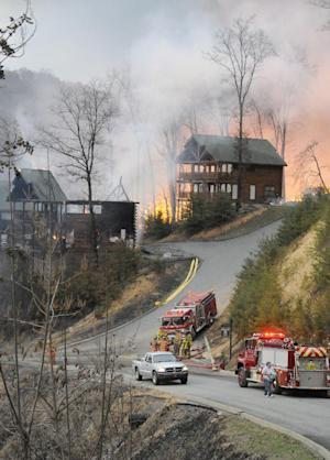 Firefighters set a boundary as cabins burn on Black Bear Cub Way in Sevier County, Tenn Sunday, March 17, 2013. As of 8:00 p.m. there was 32 cabins reported burned with 40 more in danger as shifting winds started breaking contain lines. (AP Photo/The Mountain,Curt Habraken) MANDATORY CREDIT