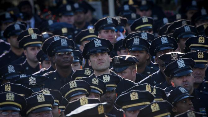 Police officers stand together in silence outside the Christ Tabernacle Church as they listen to the funeral service for slain New York Police Department (NYPD) officer Rafael Ramos in the Queens borough of New York
