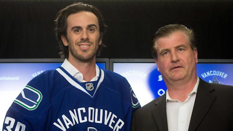 Vancouver Canucks' goalie Ryan Miller, left, stands for photos with general manager Jim Benning after Miller signed a three-year contract with the NHL hockey team, Tuesday, July 1, 2014 in Vancouver, British Columbia
