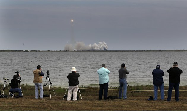 People photograph the Falcon 9 SpaceX rocket as it lifts off from launch complex 40 at the Cape Canaveral Air Force Station in Cape Canaveral, Fla. on Friday, March 1, 2013. The rocket is transporting