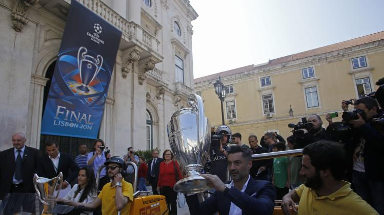 Former Portuguese soccer player Baia and Jorge, former coach of the Portuguese women's national team, sit with the Champions League and the women's Champions League trophies respectively in Lisbon