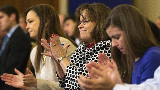 From left, Jenny Beth Martin, cofounder of the Tea Party Patriots, Jo Anne Livingston, and Darcy Crisp, all of Atlanta, applaud after House Ways and Means Committee member Rep. Aaron Schock, R-Ill. said the IRS was discriminating, Tuesday, June 4, 2013, on Capitol Hill in Washington, during the committee's hearing of organizations that say they were unfairly targeted by the Internal Revenue Service while seeking tax-exempt status. (AP Photo/Jacquelyn Martin)