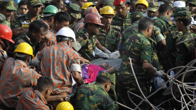 Rescuers carry a survivor pulled out from the rubble of a building that collapsed in Saver, near Dhaka, Bangladesh, Friday, May 10, 2013. Rescue workers in Bangladesh freed the woman buried for 17 days inside the wreckage of a garment factory building that collapsed, killing more than 1,000 people. Soldiers at the site said her name was Reshma and described her as being in remarkably good shape despite her ordeal. (AP Photo/Rahul Talukder)