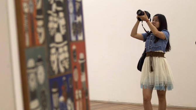 A woman takes pictures during a visit for journalists to the Rio Art Museum before its inauguration in Rio de Janeiro, Brazil, Thursday, Feb. 28, 2013. The museum, scheduled to open on Friday, is part of Rio's multi-billion dollar bid to reinvent itself before playing host to a double header of mega-events, the 2014 World Cup soccer tournament and the 2016 Olympics. (AP Photo/Silvia Izquierdo)