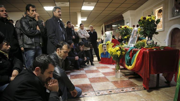 "Men react inside the Kurdish cultural center in Paris, Thursday, Jan. 10, 2013. Three Kurdish women including Sakine Cansiz one of the founders of a militant group battling Turkish troops since 1984, were ""executed"" at a Kurdish center in Paris, the interior minister said Thursday. (AP Photo/Christophe Ena)"