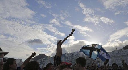 Argentina holds up a replica of the World Cup trophy on Copacabana beach ahead of Sunday's World Cup final match between Argentina and Germany in Rio de Janeiro