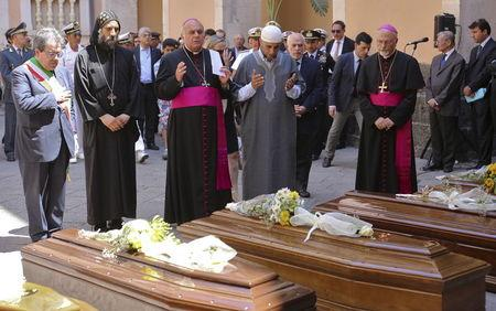 Local civil and religious representatives pray in front of the coffins of 13 unidentified migrants who died in the April 19, 2015 shipwreck, during an inter-faith funeral service in Catania