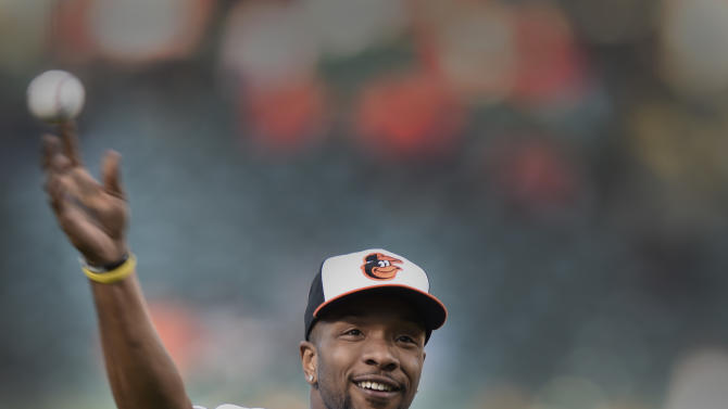 Maryland basketball player Dez Wells throws out the first pitch before the Orioles play the Boston Red Sox in a baseball game, Friday, April 24, 2015, in Baltimore.(AP Photo/Gail Burton)