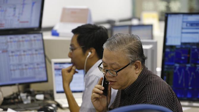 A broker talks on phone at a brokerage firm in Hong Kong, Wednesday, July 8, 2015. The Hang Seng Index has dropped in morning trading following more big losses on mainland markets. Chinese stocks led a slump in Asian markets on Wednesday as the sell-off in Shanghai intensified and Greece's future in the euro remained highly uncertain.  (AP Photo/Kin Cheung)