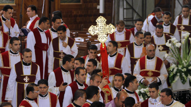 Egyptian church choir hold a cross as they prepare to receive Pope Tawadros II, the 118th pope of the Coptic Church of Egypt, not pictured, to lead the Easter Mass at St. Mark's Cathedral in Cairo, Egypt, late Saturday May 4, 2013. Egypt's Coptic Christians, who make up about 10 percent of the country's 85 million people, have long complained of discrimination by the state. They are the largest Christian community in the Middle East.  (AP Photo/ Amr Nabil)