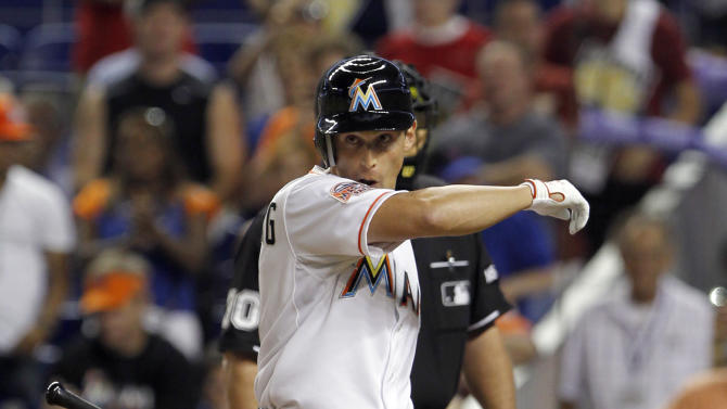Miami Marlins' Adam Greenberg wipes his face as he heads to the dugout after striking out against the New York Mets in the sixth inning of a baseball game in Miami, Tuesday, Oct. 2, 2012. Returning to the big leagues seven years after he was beaned, Greenberg fanned on three pitches as a pinch-hitter. He signed a one-day contract before the game and batted leading off the sixth inning against Mets 20-game winner R.A. Dickey. (AP Photo/Alan Diaz)