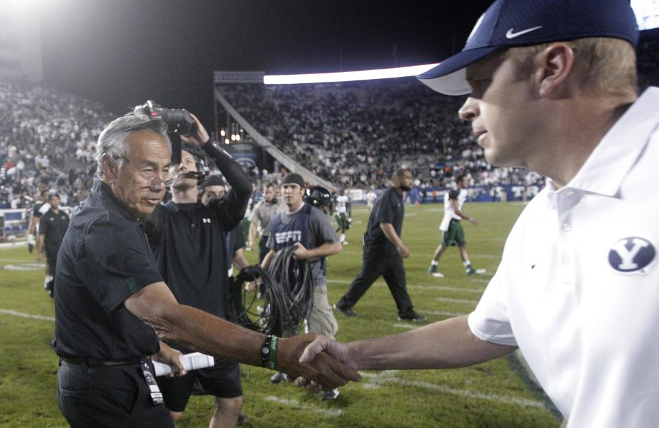 Hawaii coach Norm Chow, left, shakes hands with Brigham Young coach Bronco Mendenhall after an NCAA college football game Friday, Sept. 28, 2012, in Provo, Utah. BYU defeated Hawaii 47-0. (AP Photo/Rick Bowmer)