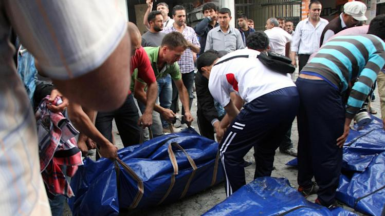 People prepare to carry bodies of victims after several explosions killed at least 40 people and injured dozens in Reyhanli, near Turkey's border with Syria, Saturday, May 11, 2013, Turkish Interior Minister Muammer Guler said. (AP Photo/IHA) TURKEY OUT