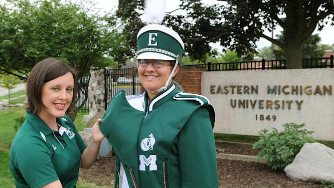 In this image provided by Eastern Michigan University, Amy Knopps, left marching band director, shows off the Huron and Normalite logos imbedded in the schools' new marching band uniforms that is worn by uniforn manager Maria Eloff, Friday, Sept. 7, 2012, in Ypsilanti, Mich. When the Eastern Michigan University football team takes the field for its home opener this weekend, members of the school marching band will be sporting uniforms emblazoned with two of EMU's former logos, including one the school dropped 21 years ago amid criticism it was demeaning to Native Americans. (AP Photo/Eastern Michigan University, Randy Mascharka)