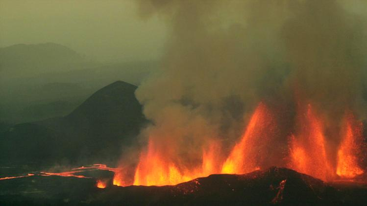 FILE - In this Sunday, July 28, 2002 file photo, plumes of lava spew high into the air from Mount Nyamulagira, near the town of Goma in eastern Congo. Virunga National Park is inviting tourists on an overnight trek to view a spectacular eruption of Mount Nyamulagira, where rivers of incandescent lava are flowing slowly north into an uninhabited part of the park and pose no danger to its critically endangered mountain gorillas, in eastern Congo. (AP Photo/Sayyid Azim, File)