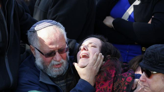 A family member mourns during the funeral for Captain Yochai Kalangel at Mount Herzl military cemetery in Jerusalem