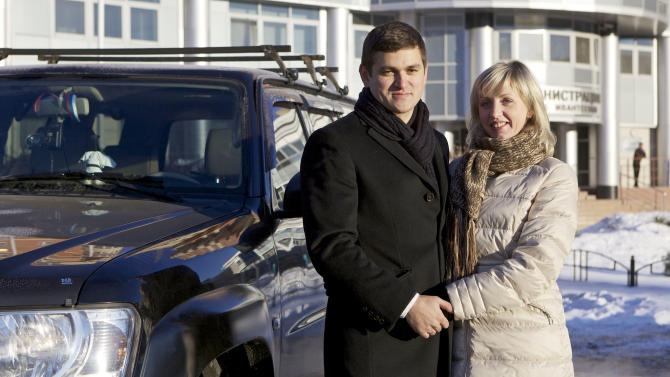 In this Dec. 17, 2012, photo, construction company owner Timur Bulgakov and his ethnically Russian wife Yevgeniya pose for a photo near their car in Ivanteyevka, Russia, a Moscow suburb. The old Moscow is rapidly giving way to a multi-ethnic city where Muslims from Central Asia are the fastest growing sector of the population. (AP Photo/Alexander Zemlianichenko Jr)