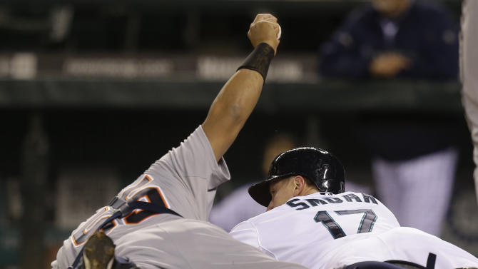 Seattle Mariners' Justin Smoak looks over as Detroit Tigers catcher Brayan Pena holds up the ball after getting Smoak out at the plate in the 14th inning of a baseball game, Wednesday, April 17, 2013, in Seattle. The Tigers beat the Mariners 2-1 in 14 innings. (AP Photo/Ted S. Warren)