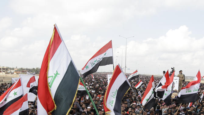 Iraqis chant anti-government slogans as they wave national flags during a protest in Fallujah, 40 miles (65 kilometers) west of Baghdad, Iraq, Friday, Feb. 1, 2013. Tens of thousands of Sunni protesters blocked a major highway in western Iraq on Friday, as an al-Qaida-affiliated group called on Sunnis to take up arms against the Shiite-led government. (AP Photo/Khalid Mohammed)