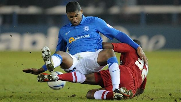 Peterborough United's Mark Little (facing) and Charlton Athletic's Callum Harriott (back) battle for the ball. (PA Photos)
