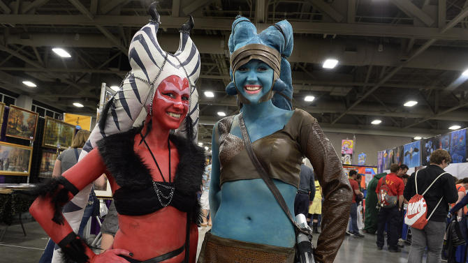 """Hope Twede, left as a Sith, and Jessica Johnson, as Jedi """"Ayala Secura"""" pose for a photo on the floor at the opening day of Salt Lake Comic Con, Thursday, April 17, 2014, in Salt Lake City, Utah. (AP Photo/The Salt Lake Tribune, Scott Sommerdorf)"""