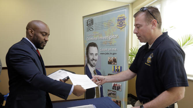 In this Feb. 6, 2015 photo, U.S. Marine Corps Veteran Arlington Robertson, of Fort Lauderdale, left, hands his resume to an Internal Revenue Service Special Agent, at the annual Veterans Career and Resource Fair in Miami. The Labor Department releases employment data for February on Friday, March 6, 2015. (AP Photo/Alan Diaz)