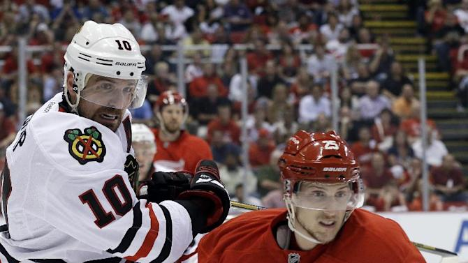 Chicago Blackhawks center Patrick Sharp (10) and Detroit Red Wings center Cory Emmerton (25) battle for the puck during the first period of an NHL hockey Stanley Cup playoffs Western Conference semifinal game in Detroit, Monday, May 20, 2013. (AP Photo/Paul Sancya)