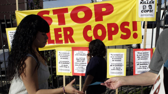 An activist passes out flyers during a protest against Los Angeles Police Department in Los Angeles, Tuesday, March 15, 2011. The Los Angeles Police Commission says an LAPD officer was justified in killing a Guatemalan immigrant last year, a shooting that sparked days of protest in the Latino community. Police said the 37-year-old day laborer had a knife and lunged toward the officer after refusing orders in Spanish and English to drop the weapon. (AP Photo)