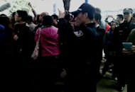 A policeman films as demonstrators call for press freedom in support of journalists from the Southern Weekend newspaper outside the company&#39;s office building in Guangzhou, south China&#39;s Guangdong province on January 8, 2013