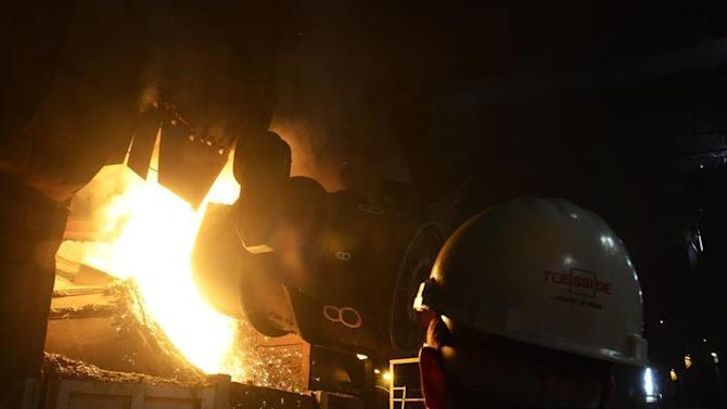 A ladle of iron is poured into a basic oxygen steel making vessel at the SSI steel plant at Redcar