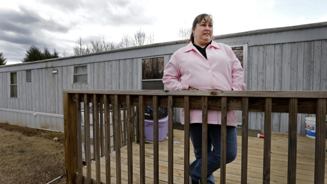 In this Feb. 28, 2013 photo, Sarah Chavez stands on the porch of her home in Lexington, N.C. Desperate to raise money for their 6-year-old daughter's cancer treatments last summer, friends told Jose and Sarah Chavez of a way to quickly turn their meager savings into a small fortune. But what the Chavez family and many others didn't know was that state and federal regulators for months had received complaints that ZeekRewards was a scam. (AP Photo/Chuck Burton)