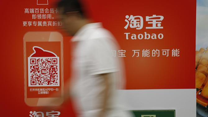 A man walks past an advertising billboard showing the mobile app of Alibaba's Taobao consumer-to-consumer site at a subway station in Beijing Thursday, Sept. 18, 2014. Alibaba Group's U.S. stock offering is a wakeup call about an emerging wave of technology giants in China's state-dominated economy. (AP Photo/Vincent Thian)