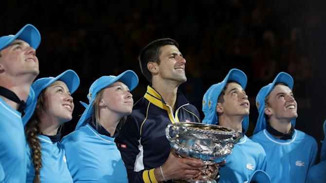 Serbia's Novak Djokovic poses with ball boys and ball girls after defeating Britain's Andy Murray in the men's final at the Australian Open tennis championship in Melbourne, Australia, Monday, Jan. 28, 2013. (AP Photo/Aaron Favila)