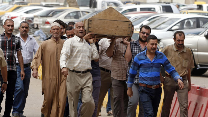 Mourners carry the coffin of a man killed due to Tuesday's liquor stores attack in Baghdad, Iraq, Wednesday, May 15, 2013. A convoy of gunmen opened fire on a row of liquor stores in eastern Baghdad immediately after sunset on Tuesday, killing many and wounding several others, officials said. (AP Photo/ Karim Kadim)