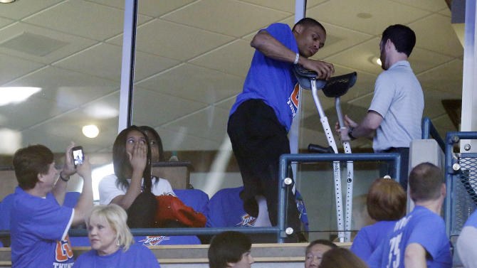 A fan, lower left, takes an image of Oklahoma City Thunder guard Russell Westbrook, center, as he gets back on his crutches at the end of the second quarter of Game 5 of the Thunder's first-round NBA basketball playoff series against the Houston Rockets in Oklahoma City, Wednesday, May 1, 2013. Westbrook, who is injured, was watching the game from the suite level. (AP Photo/Sue Ogrocki)