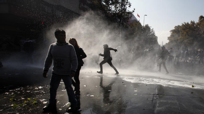 People walk through the spray of a police water cannon after clashes broke out between protesters and security forces at the annual May Day march in Santiago, Chile, Wednesday, May 1, 2013.  In protests, parades, strikes and other demonstrations held in cities across the planet, activists lashed out at political and business leaders they allege have ignored workers' voices or enriched themselves at the expense of laborers during what has been a difficult few years for the global economy. (AP Photo/Luis Hidalgo)