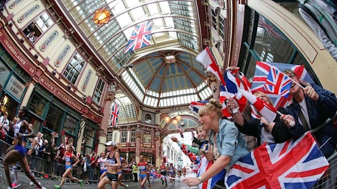 Runners pass through the historic landmark of Leadenhall Market in London during the women's marathon at the 2012 Summer Olympics on Sunday, Aug. 5, 2012. (AP Photo/Julien Behal, PA) UNITED KINGDOM OUT; NO SALES; NO ARCHIVE