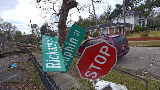 A street sign is bent at a severe angle from a Christmas Day tornado as residents clean up and assess the damage Wednesday, Dec. 26, 2012  in Mobile, Ala. With only a handful of injuries and no deaths reported statewide from the storms, the head of the state's emergency response said it was difficult to fathom how the toll wasn't worse. (AP Photo/G.M. Andrews)