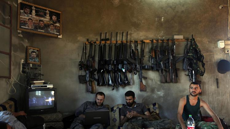 FILE - Free Syrian Army fighters sit in a house on the outskirts of Aleppo, Syria, June 12, 2012. This image was one in a series of 20 by AP photographers that won the 2013 Pulitzer Prize in Breaking News Photography. (AP Photo/Khalil Hamra, File)