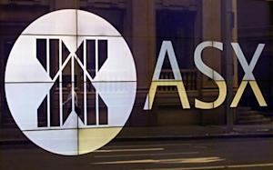 An office worker walks past the board of the Australian Securities Exchange building displaying its logo in central Sydney