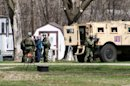 This May 3, 2013, photo provided by Jeremy Jones shows FBI agents with Buford Rogers, back left, and an unidentified man during a raid on a mobile home in Montevideo, Minn. Authorities said Monday, May 6, that Rogers was arrested Friday and that the agency believes is disrupted a potential terror attack after a search of the home turned up Molotov cocktails, suspected pipe bombs and firearms. (AP Photo/Montevideo American-News, Jeremy Jones) MANDATORY CREDIT