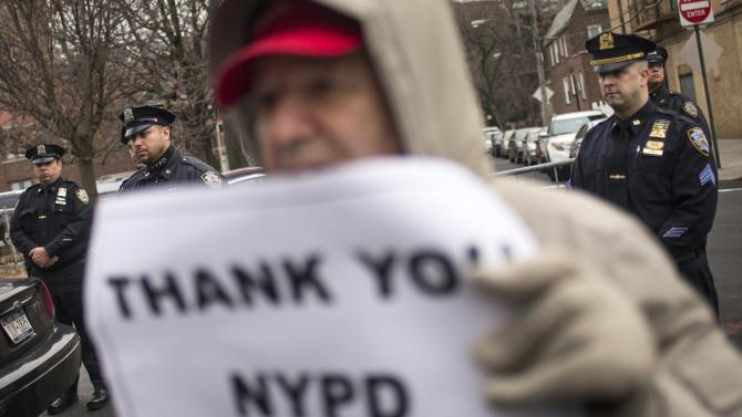 New York Police Department (NYPD) officers stand nearby as a man holds a sign while gathered with dozens  to show support for policemen