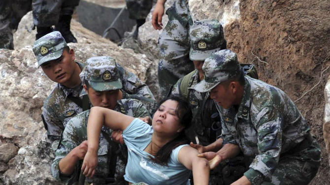 In this photo released by China's Xinhua news agency, rescuers save an injured woman after an earthquake hit Baosheng Township in Lushan County, Ya'an City, southwest China's Sichuan Province, Saturday, April 20, 2013. The powerful earthquake struck the steep hills of Sichuan province Saturday, nearly five years after a devastating quake wreaked widespread damage across the region. (AP Photo/Xinhua, Jiang Hongjing) NO SALES