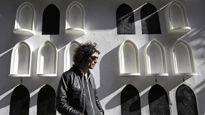 This Oct. 24, 2013 photo shows The Strokes' drummer Fabrizio Moretti in front of his installation on the exterior wall of the SoHo Rag & Bone store in New York. The installation is part of the clothing brand's ongoing urban art project, in which they get artists to revamp the store's façade. (AP Photo/Kathy Willens)