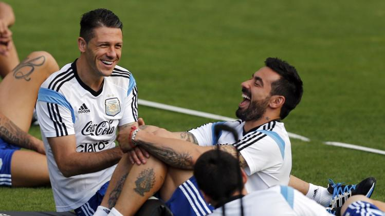 Argentina's Demichelis and Lavezzi laugh next to Messi during a training session ahead of their 2014 World Cup final match against Germany in Vespasiano