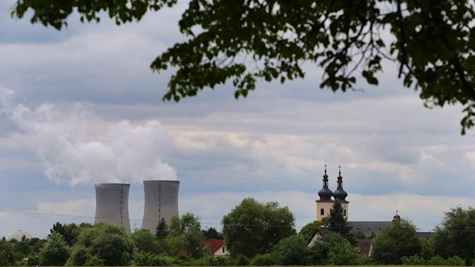 FILE - In this May 27, 2015 file photo a catholic church is pictured next to the nuclear power plant in Grafenheinfeld, southern Germany. Bavaria's environment ministry said Sunday, June 28, 2015, Germany's oldest remaining nuclear reactor has been shut down, part of a move initiated four years ago to switch off all its nuclear plants by 2022. (Karl-Josef Hildenbrand/dpa via AP, File)