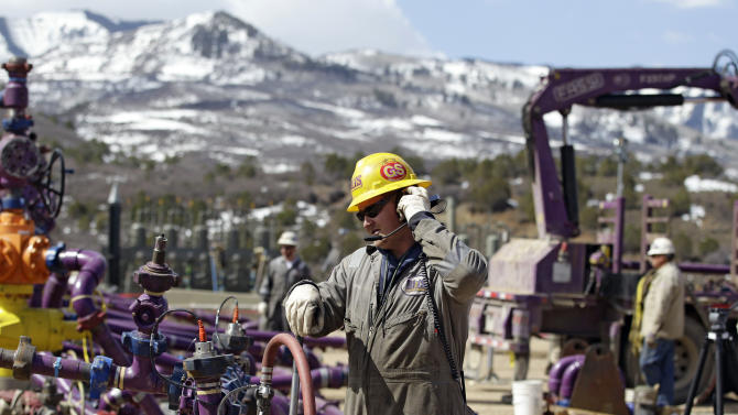 In this March 29, 2013 photo, a worker uses a headset and microphone to communicate with coworkers over the din of pump trucks, at the site of a natural gas hydraulic fracturing and extraction operation run by the Encana Oil & Gas (USA) Inc., outside Rifle, in western Colorado. Technology created an energy revolution over the past decade, but Old Energy is winning. Oil companies big and small have used technology to find a bounty of oil and natural gas so large that worries about running out have melted away.  (AP Photo/Brennan Linsley)
