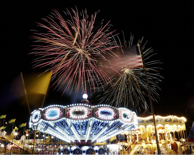 A United States flag waves next to carnival rides as fireworks burst in the air during the Fourth of July Independence Day show at State Fair Meadowlands, Tuesday, July 3, 2012, in East Rutherford, N.