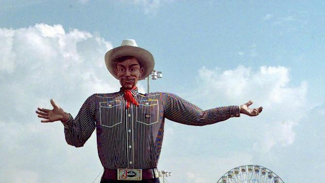 FILE - In this Oct. 6, 1997 file photo, Big Tex watches over the crowd at one end of the Texas State Fair midway in Dallas. Fire destroyed Big Tex on Friday, Oct. 19, leaving behind little more than the metal frame of the 52-foot-tall metal-and-fabric cowboy that is an icon of the State Fair of Texas. (AP Photo/Bill Janscha, File)
